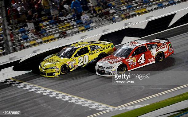 Matt Kenseth driver of the Dollar General Toyota leads Kevin Harvick driver of the Budweiser Chevrolet to the finish to win the NASCAR Sprint Cup...