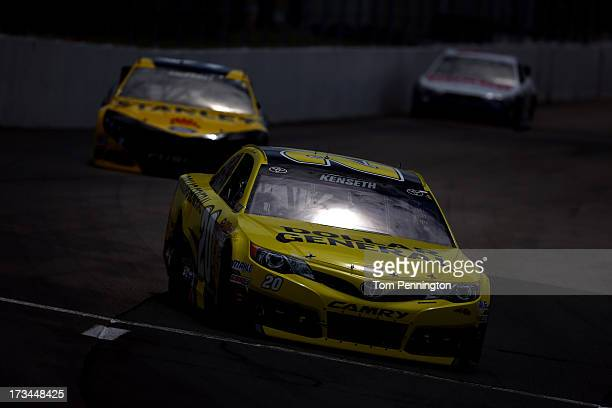 Matt Kenseth, driver of the Dollar General Toyota, leads Marcos Ambrose, driver of the Stanley Ford, during the NASCAR Sprint Cup Series Camping...