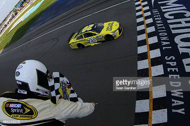 Matt Kenseth driver of the Dollar General Toyota takes the checkered flag to win the NASCAR Sprint Cup Series Pure Michigan 400 at Michigan...