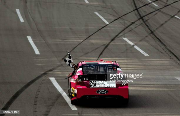 Matt Kenseth driver of the Ford Ecoboost/National Breast Cancer Foundation Ford celebrates with the checkered flag after winning the NASCAR Sprint...