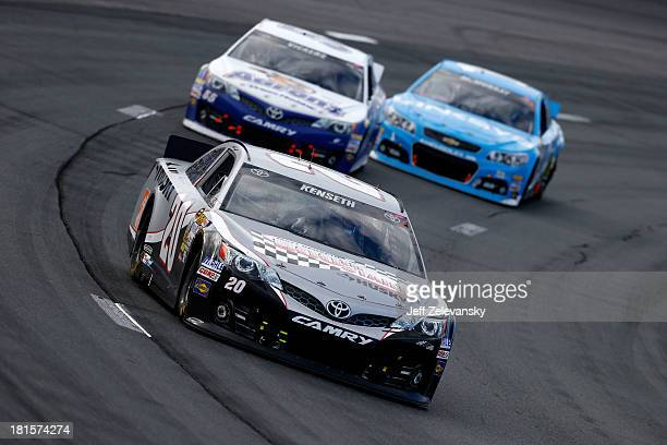 Matt Kenseth, driver of the Home Depot / Husky Toyota, leads Brian Vickers, driver of the Aaron's Dream Machine Toyota, and Jamie McMurray, driver of...