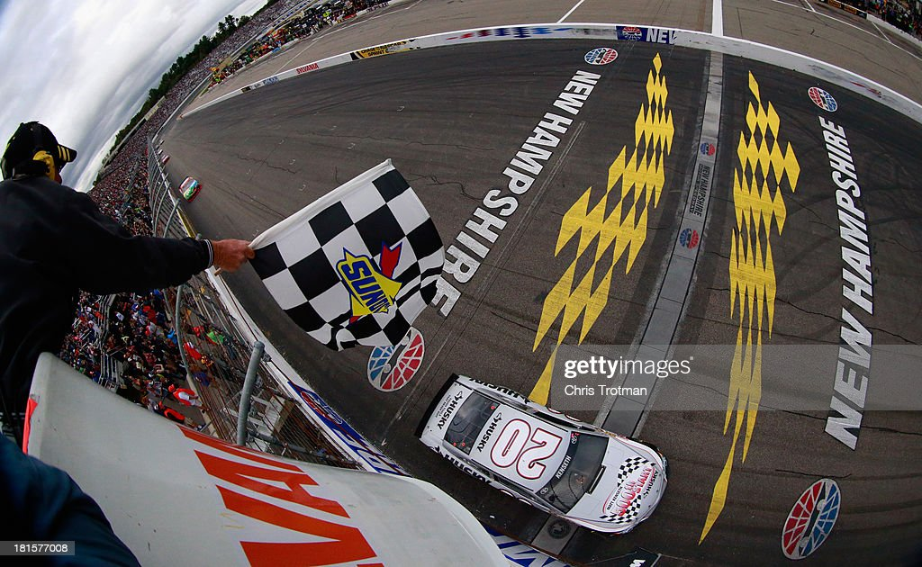 Matt Kenseth, driver of the #20 Home Depot / Husky Toyota, takes the checkered flag as he crosses the finish line to win the NASCAR Sprint Cup Series Sylvania 300 at New Hampshire Motor Speedway on September 22, 2013 in Loudon, New Hampshire.