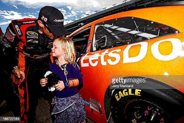 """Matt Kenseth, driver of the Home Depot """"Let's Do This"""" Toyota, kisses daughter Kaylin during pre-race ceremonies for the NASCAR Sprint Cup Series AAA..."""