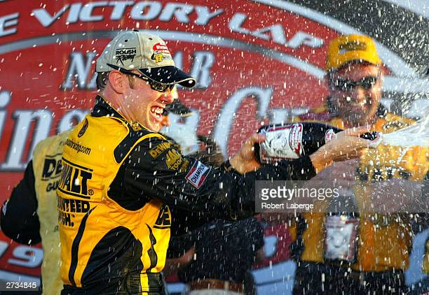 Matt Kenseth driver of the Roush Racing DeWalt Power Tools Ford sprays champagne to celebrate winning the NASCAR Winston Cup Championship after the...