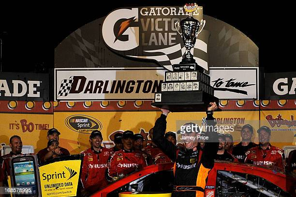 Matt Kenseth driver of the The Home Depot / Husky Toyota celebrates with the trophy and his crew in victory lane after winning the NASCAR Sprint Cup...