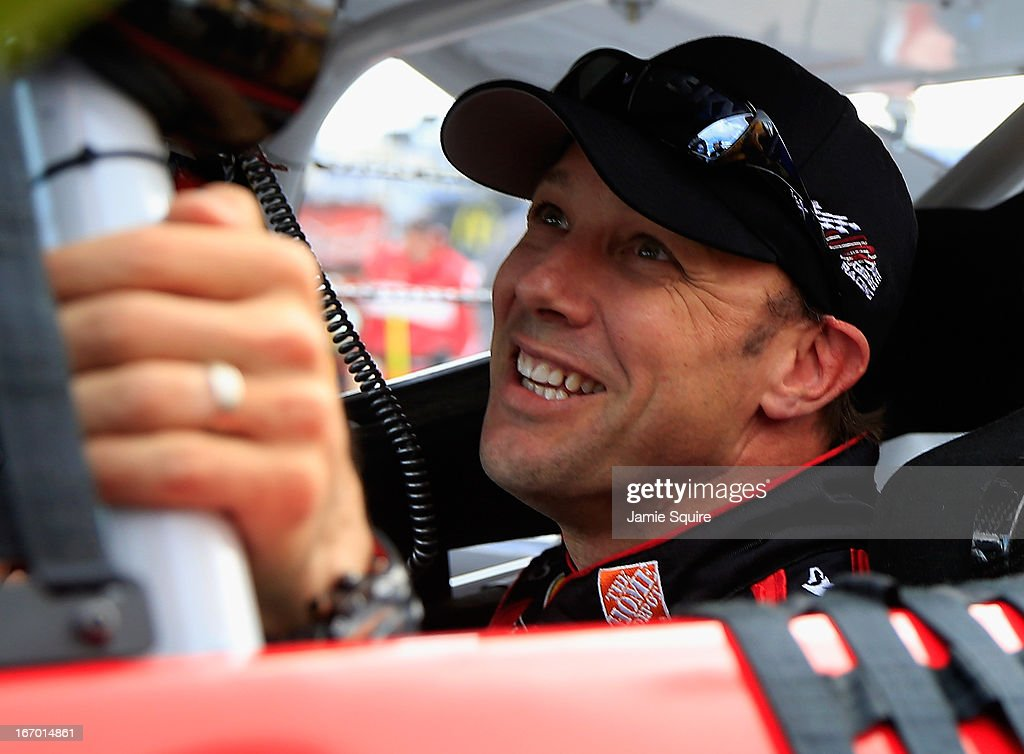 Matt Kenseth, driver of the #20 The Home Depot/Husky Toyota, climbs out of his car on the grid after qualifying for pole position for the NASCAR Sprint Cup Series STP 400 at Kansas Speedway on April 19, 2013 in Kansas City, Kansas.