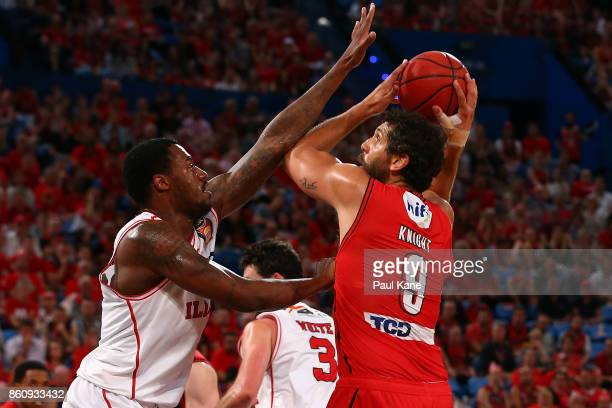 Matt Knight of the Wildcats looks to put a shot up against Delvon Johnson of the Hawks during the round two NBL match between the Perth Wildcats and...