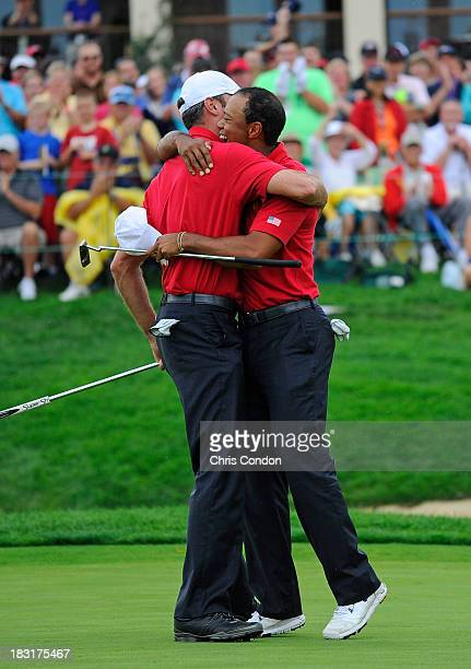 Matt Kuchar and Tiger Woods celebrate after winning their match during the Day Three Fourball Matches of The Presidents Cup at Muirfield Village Golf...