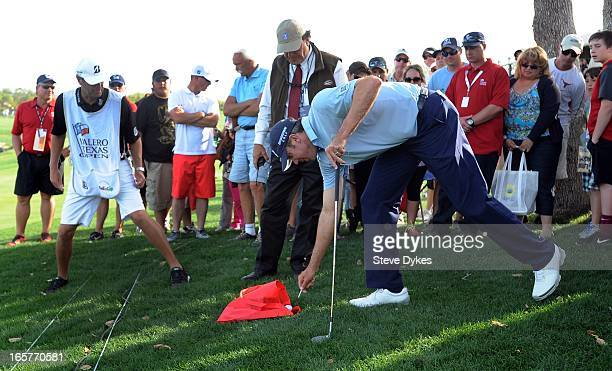 Matt Kuchar marks his ball which landed in a spectator's bag on the 18th hole during the second round of the Valero Texas Open at the ATT Oaks Course...