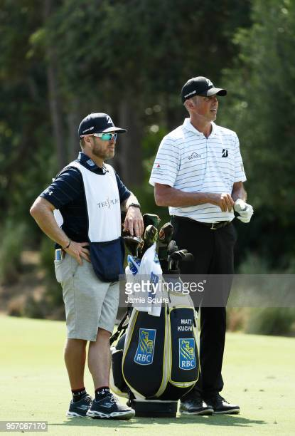 Matt Kuchar of the United States and caddie John Wood prepare to play a shot on the tenth hole during the first round of THE PLAYERS Championship on...