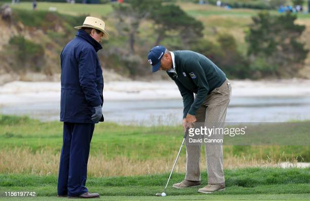 Matt Kuchar of the United States gets a ruling from Slugger White after he had tried to get a drop from a USGA rules official on the par 3 17th hole...