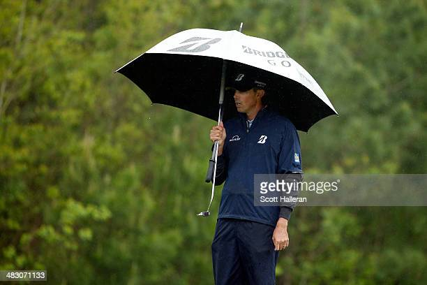 Matt Kuchar of the United States holds an umbrella as rain falls on the green of the eighth hole during the final round of the Shell Houston Open at...
