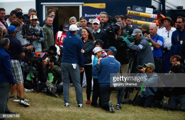 Matt Kuchar of the United States hugs his children as his wife Sybi Kuchar congratulates Jordan Spieth of the United States on the 18th green during...