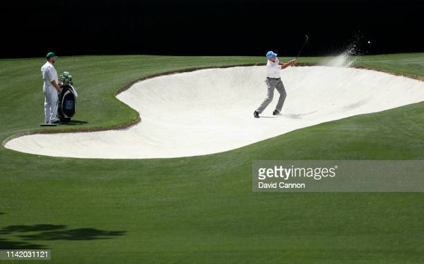 Matt Kuchar of the United States plays a shot from a bunker on the fourth hole during the first round of the Masters at Augusta National Golf Club on...