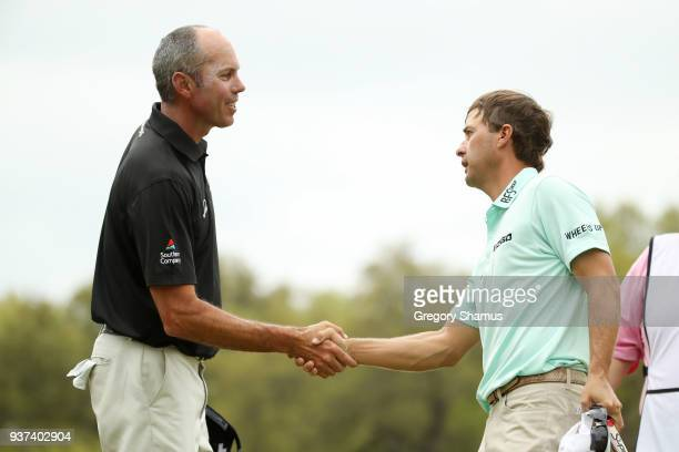 Matt Kuchar of the United States shakes hands with Kevin Kisner of the United States after being defeated by him 1up on the 18th green during the...