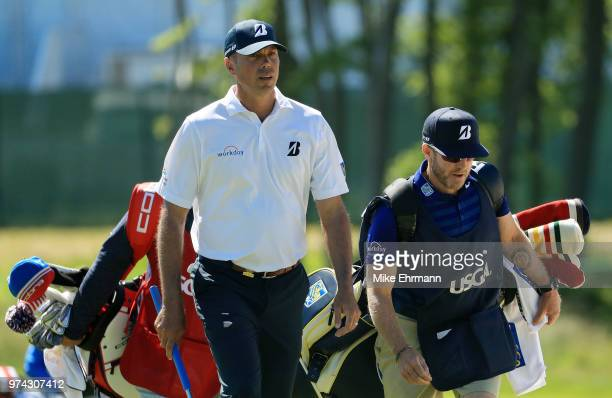 Matt Kuchar of the United States walks with caddie John Wood on the sixth hole during the first round of the 2018 US Open at Shinnecock Hills Golf...