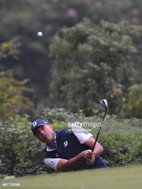 Matt Kuchar of the US hits a chip shot during the final round of the 975 million USD WGCHSBC Champions at the Sheshan International golf club in...