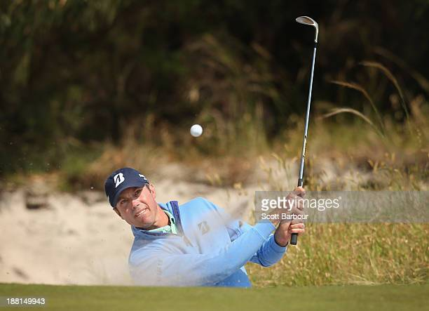 Matt Kuchar of the USA plays out of a bunker on the 15th hole during round three of the 2013 Australian Masters at Royal Melbourne Golf Course on...