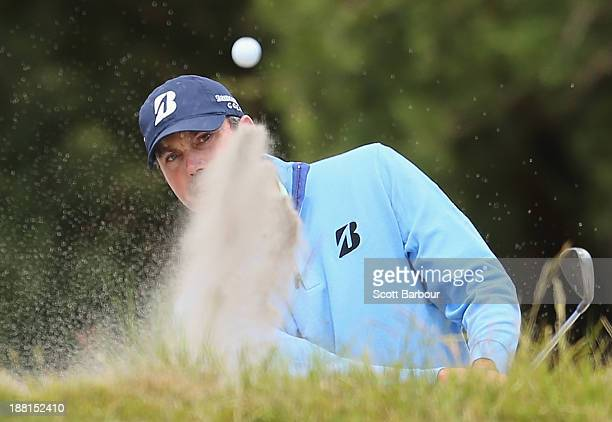 Matt Kuchar of the USA plays out of a bunker on the 7th hole during round three of the 2013 Australian Masters at Royal Melbourne Golf Course on...