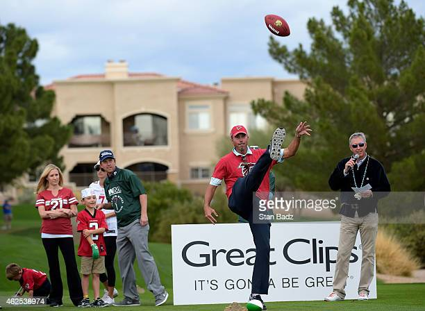 Matt Kuchar punts a football during a kicking contest at the PGA TOUR Wives Association charity golf outing during the Waste Management Phoenix Open,...