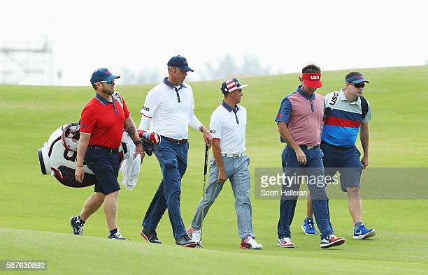 Matt Kuchar Rickie Fowler and Bubba Watson of the United States walk down a fairway with their caddies during a practice round on Day 4 of the Rio...