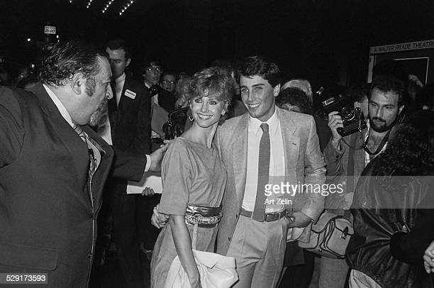Matt LaTTanzi and Olivia NewtonJohn walking through crowd to enter event circa 1970 New York