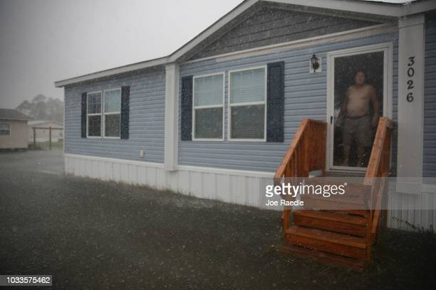 Matt Lineberry looks out the door of his home surrounded by flood waters after Hurricane Florence passed through the area on September 15, 2018 in...