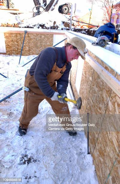 Matt Louy of Done Wright Builders pounds in wall supports before they begin to pour concrete at the home site of Julie Maren and Derek van Westrum on...