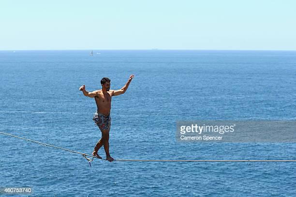 Matt Macelli walks along a slackline as he highlines between two cliffs on December 21 2014 in Sydney Australia Slacklining is a balance sport in...