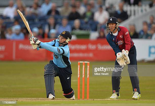 Matt Machan of Sussex hits his second six of the night as Geraint Jones of Kent look on during the Friends Life T20 match between Sussex Sharks and...