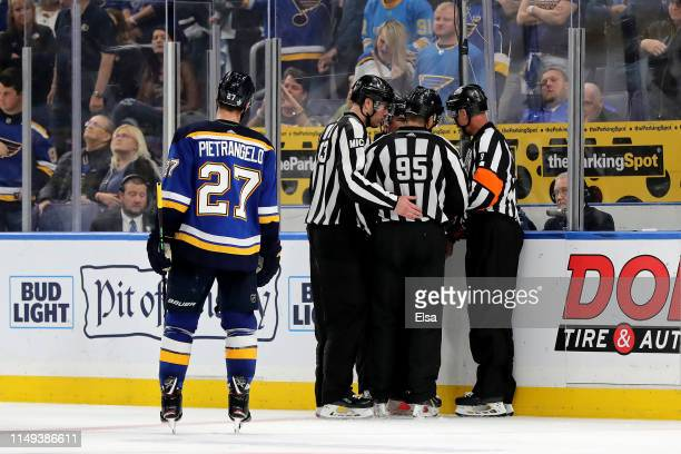 Matt MacPherson linesman Jonny Murray and referee Dan O'Rourke discuss a possible hand pass call between the San Jose Sharks and the St Louis Blues...