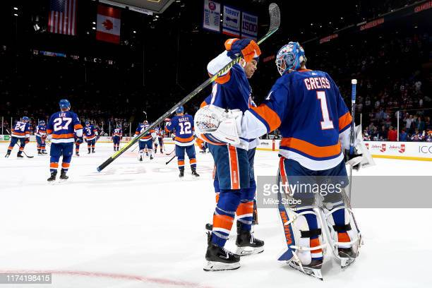 Matt Martin and Thomas Greiss of the New York Islanders celebrate their teams 4-1 win over the Winnipeg Jets at NYCB Live's Nassau Coliseum on...