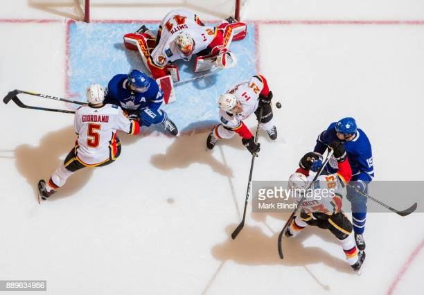 Matt Martin and Tyler Bozak of the Toronto Maple Leafs goes to the net against Sam Bennett Garnet Hathaway Mark Giordano and Mike Smith of the...