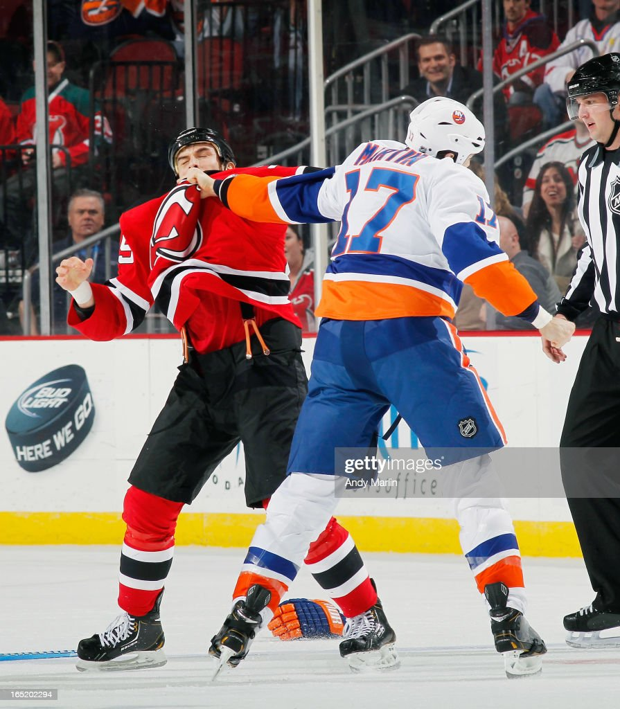 Matt Martin #17 of the New York Islanders and Tom Kostopoulos #25 of the New Jersey Devils fight during the first-period of their game at the Prudential Center on April 1, 2013 in Newark, New Jersey.