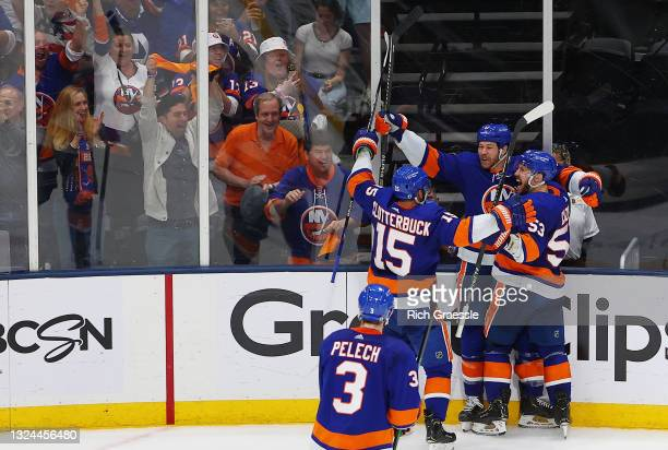 Matt Martin of the New York Islanders celebrates with Cal Clutterbuck and Casey Cizikas after scoring a goal on Andrei Vasilevskiy of the Tampa Bay...