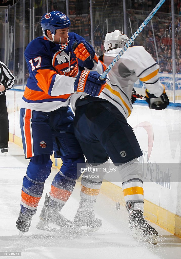 Matt Martin #17 of the New York Islanders checks Christian Ehrhoff #10 of the Buffalo Sabres into the boards at Nassau Veterans Memorial Coliseum on February 9, 2013 in Uniondale, New York.