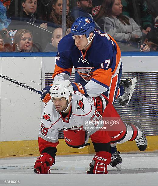 Matt Martin of the New York Islanders hits Chad LaRose of the Carolina Hurricanes in the first period at the Nassau Veterans Memorial Coliseum on...
