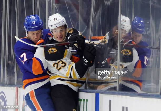 Matt Martin of the New York Islanders hits Jack Studnicka of the Boston Bruins into the boards during the third period at the Nassau Coliseum on...