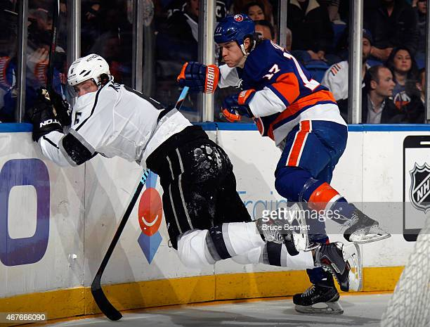 Matt Martin of the New York Islanders hits Jake Muzzin of the Los Angeles Kings into the boards during the second period at the Nassau Veterans...