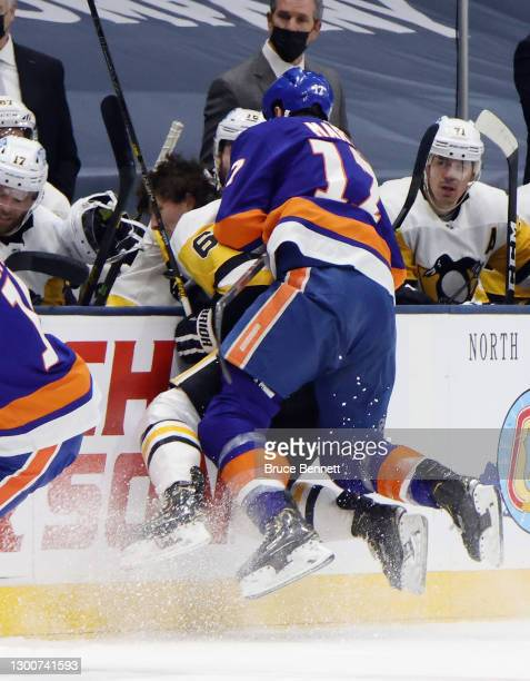 Matt Martin of the New York Islanders hits John Marino of the Pittsburgh Penguins into the bench knocking his helmet off during the first period at...