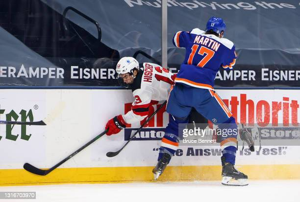 Matt Martin of the New York Islanders hits Nico Hischier of the New Jersey Devils into the boards during the second period at the Nassau Coliseum on...
