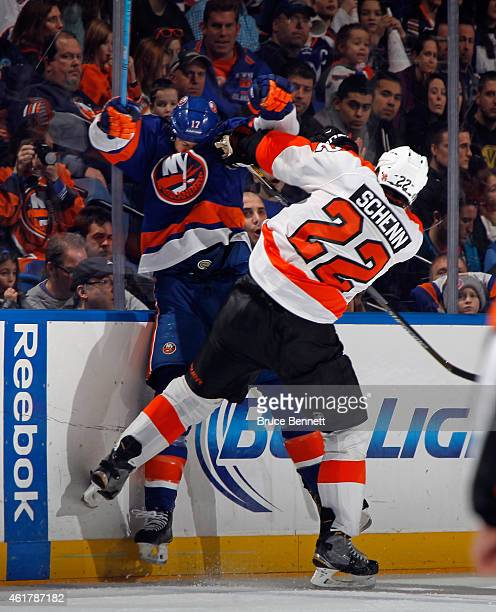 Matt Martin of the New York Islanders is hit into the boards by Luke Schenn of the Philadelphia Flyers during the third period at the Nassau Veterans...