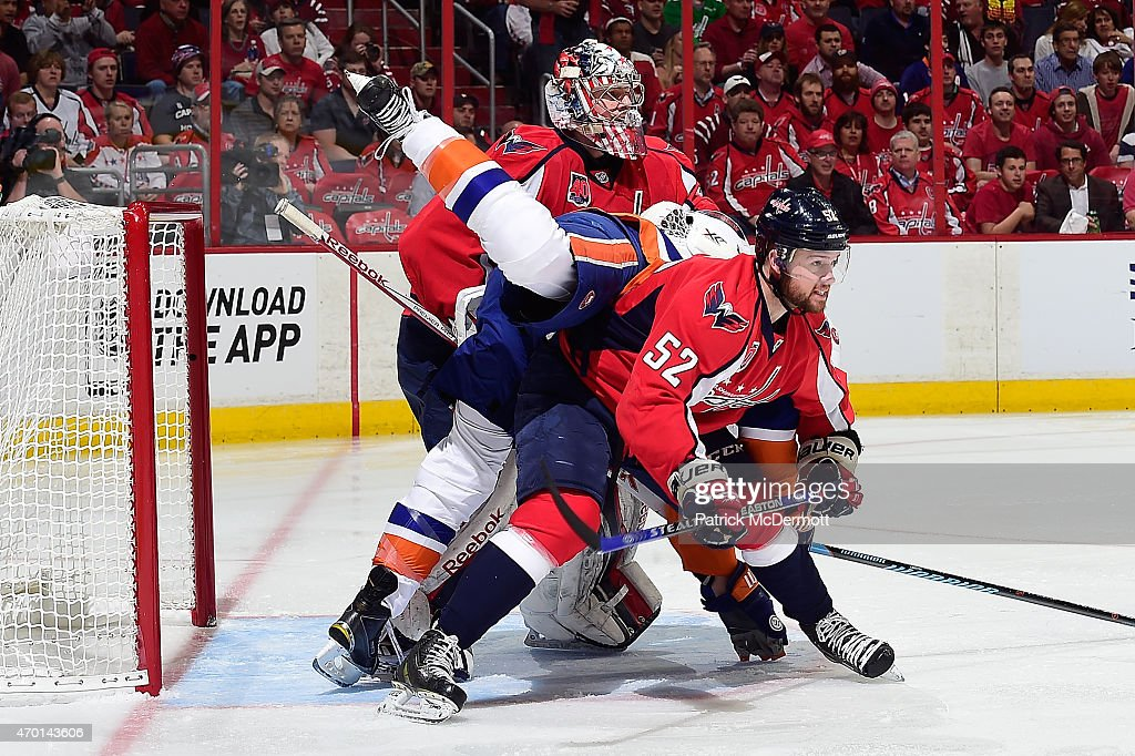 Matt Martin #17 of the New York Islanders is upended by Mike Green #52 of the Washington Capitals in front of the net during the first period in Game Two of the Eastern Conference Quarterfinals during the 2015 NHL Stanley Cup Playoffs at Verizon Center on April 17, 2015 in Washington, DC.