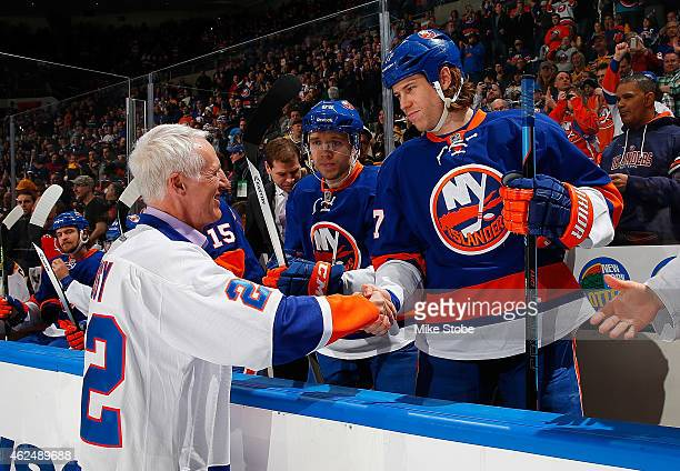 Matt Martin of the New York Islanders shakes hands with former New York Islander and Hall of Famer Mike Bossy prior to a game against the Boston...