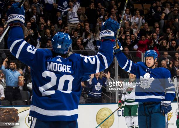 Matt Martin of the Toronto Maple Leafs and teammate Dominic Moore raise their arms after a goal by Connor Carrick of the Toronto Maple Leafs as Matt...