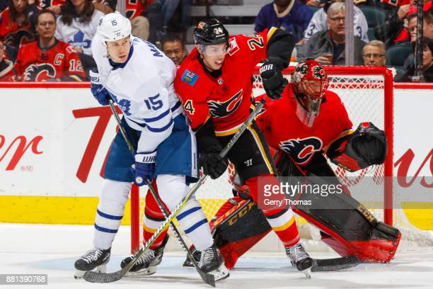 Matt Martin of the Toronto Maple Leafs and Travis Hamonic of the Calgary Flames battle for position in an NHL game against the Toronto Maple Leafs at...