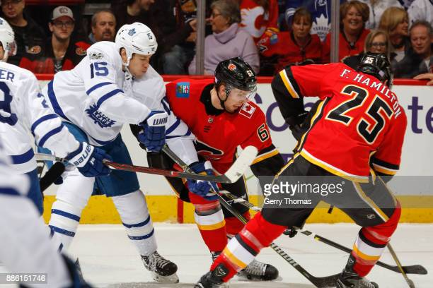 Matt Martin of the Toronto Maple Leafs Brett Kulak and Freddie Hamilton of the Calgary Flames battle for the puck in an NHL game against the Toronto...