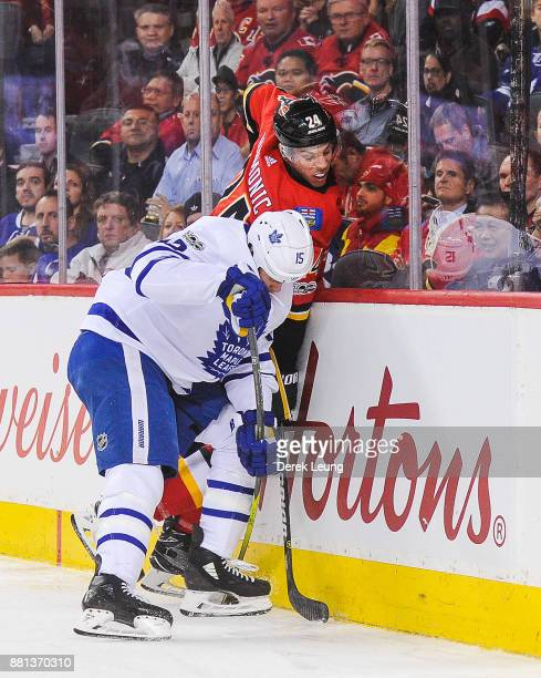 Matt Martin of the Toronto Maple Leafs checks Travis Hamonic of the Calgary Flames during an NHL game at Scotiabank Saddledome on November 28 2017 in...