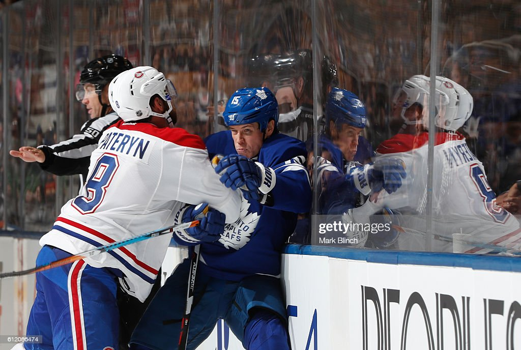 Matt Martin #15 of the Toronto Maple Leafs is checked by Greg Pateryn #8 of the Montreal Canadiens during the third period of their NHL preseason game at the Air Canada Centre on October 2, 2016 in Toronto, ON, Canada.