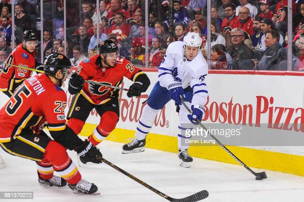Matt Martin of the Toronto Maple Leafs makes a pass before Travis Hamonic of the Calgary Flames can check him during an NHL game at Scotiabank...